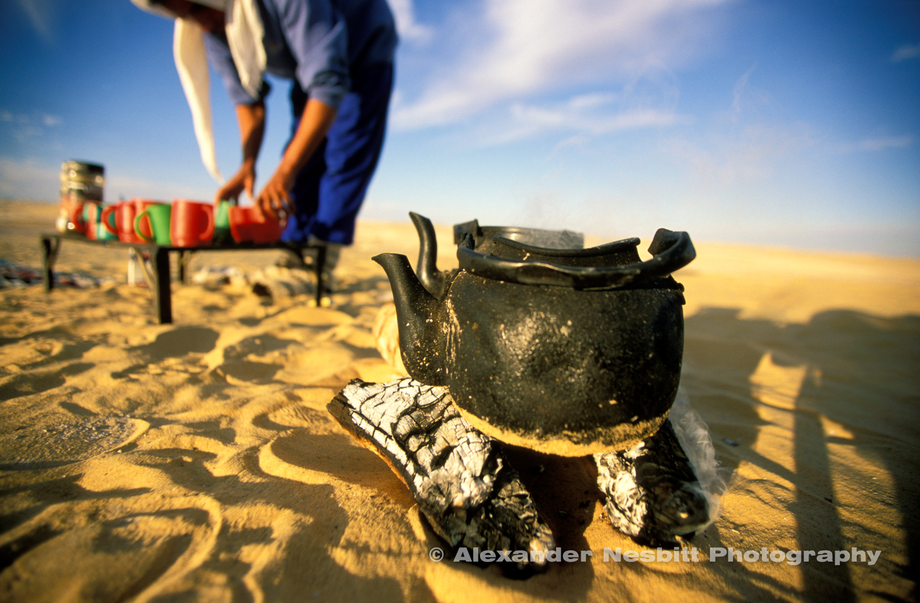 Trek guide Mohamad prepares tea in a pile of plastic cups with banged up blackened kettles boiling on a tiny, wood saving fire.  Camel trek between Farafra and Dakhla oasis, Egyptian Western desert