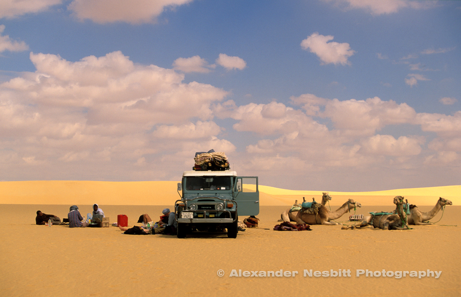 Egyptian western desert.  Lunch Time rendezvous with the supply vehicle, an old FJ40 Landcruiser, midway through a Camel trek  across the sand sea desert between Farafra and Dakhla Oasis