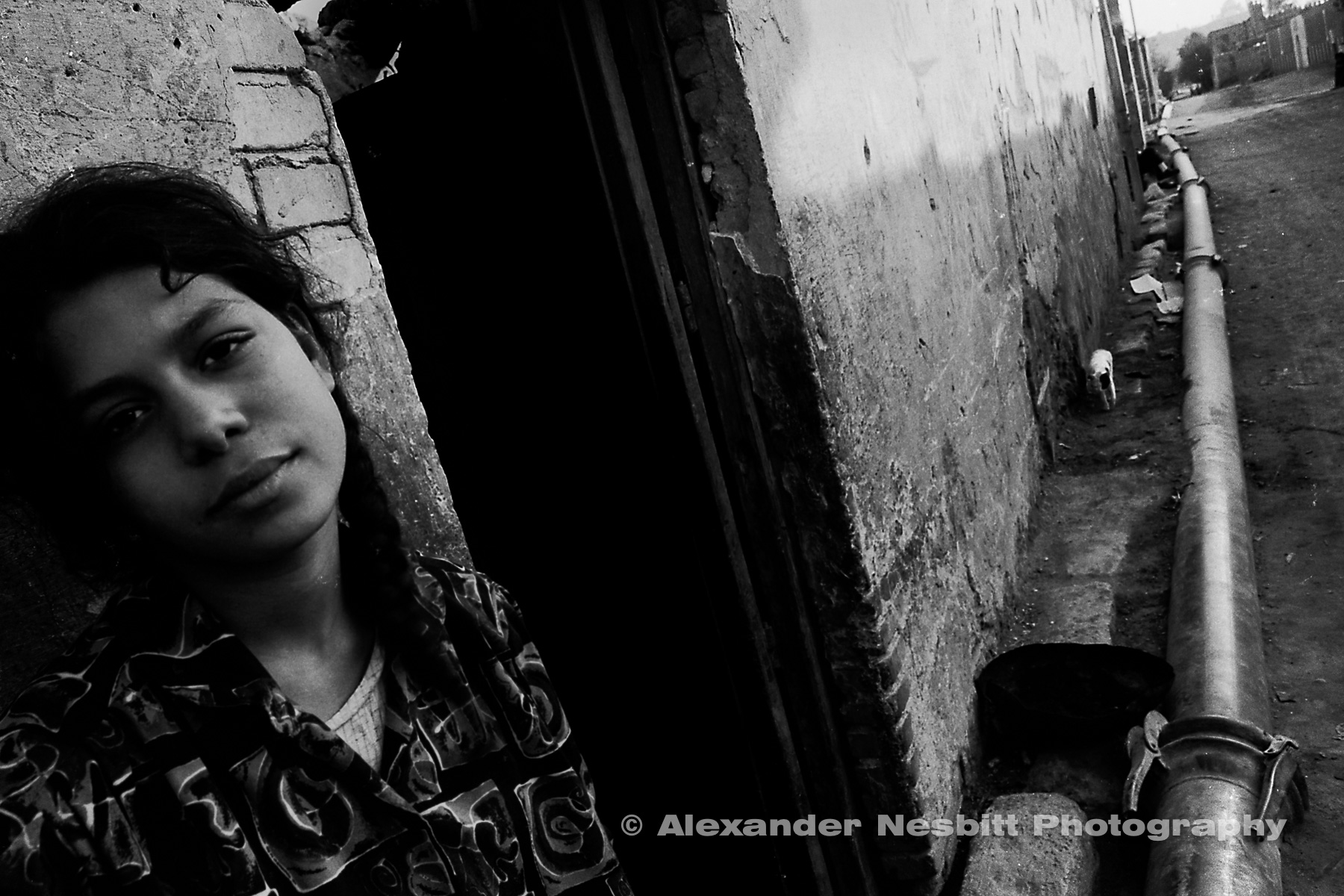 City of the Dead, Cairo - Teenage girl outside her home with the temporary water main.