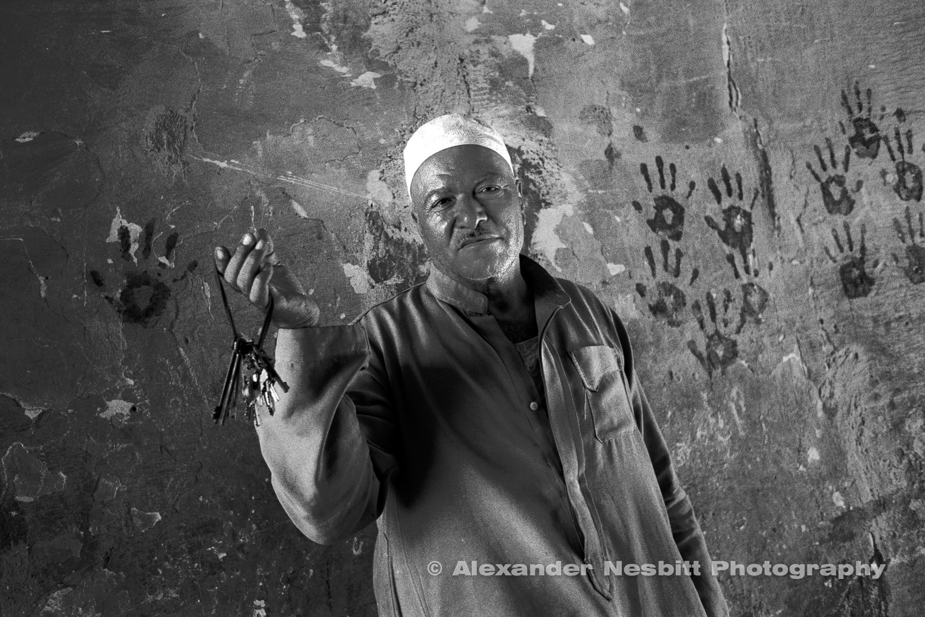 City of the Dead, Cairo - Hassan, a tomb guardian shows his ring of keys for the neighboring tombs.  Hand prints from a slaughtered sheep during the Eid el Akhtar cover the wall.