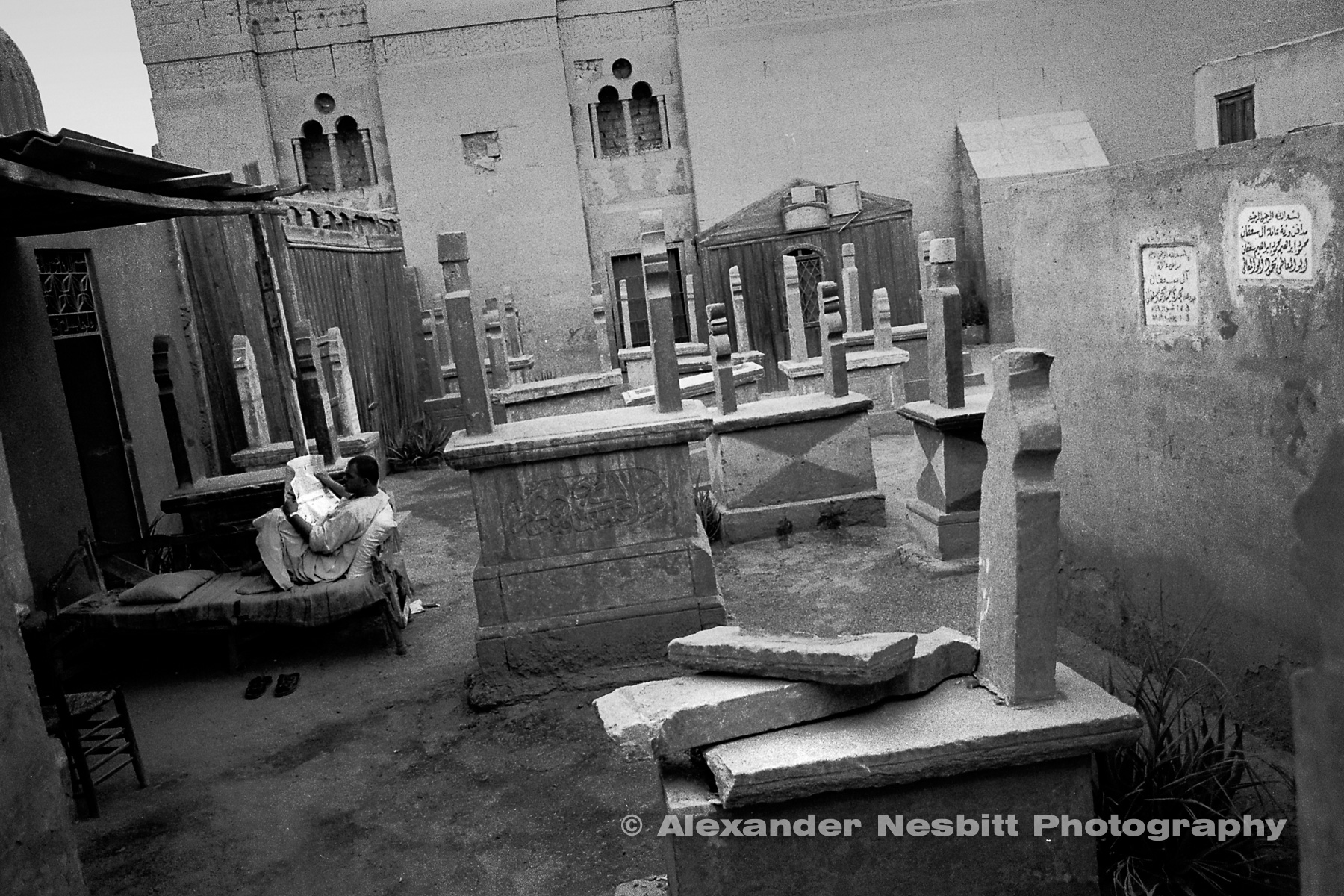 City of the Dead, Cairo  - A tomb guardian reads the paper.  For the inhabitants of the cemetery daily live goes on among the the graves.