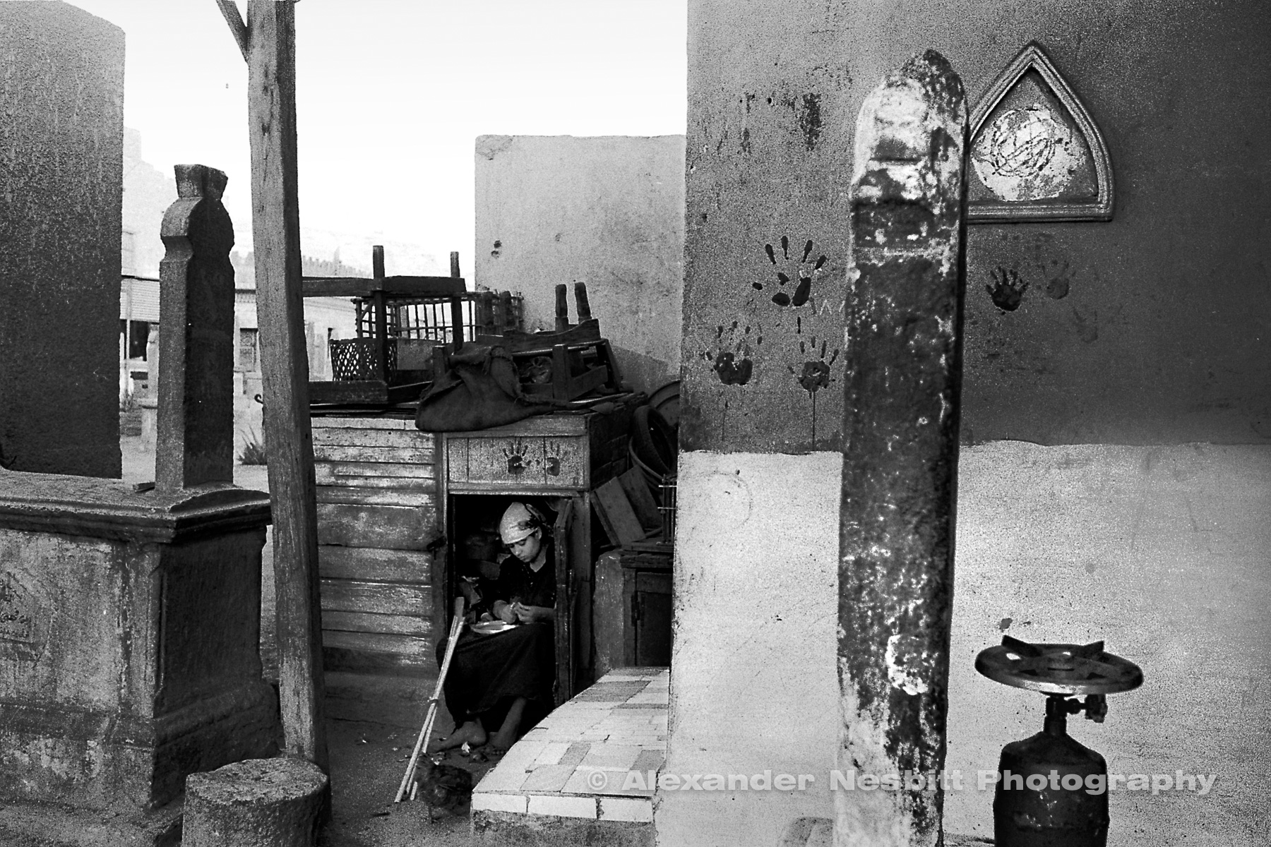 City of the Dead, Cairo  - Girl working in a make shift kitchen locker in her family compound among the grave markers.