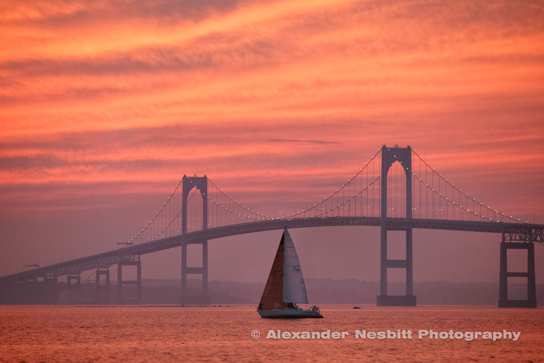 A sailor's delight as a single racing yacht aligns with the Newport Bridge under a fantastic all over pink sunset on Narragansett Bay, Newport RI