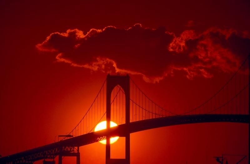 USA, Newport, RI - Sunset behind pilings of Newport Bridge in Newport Ri.