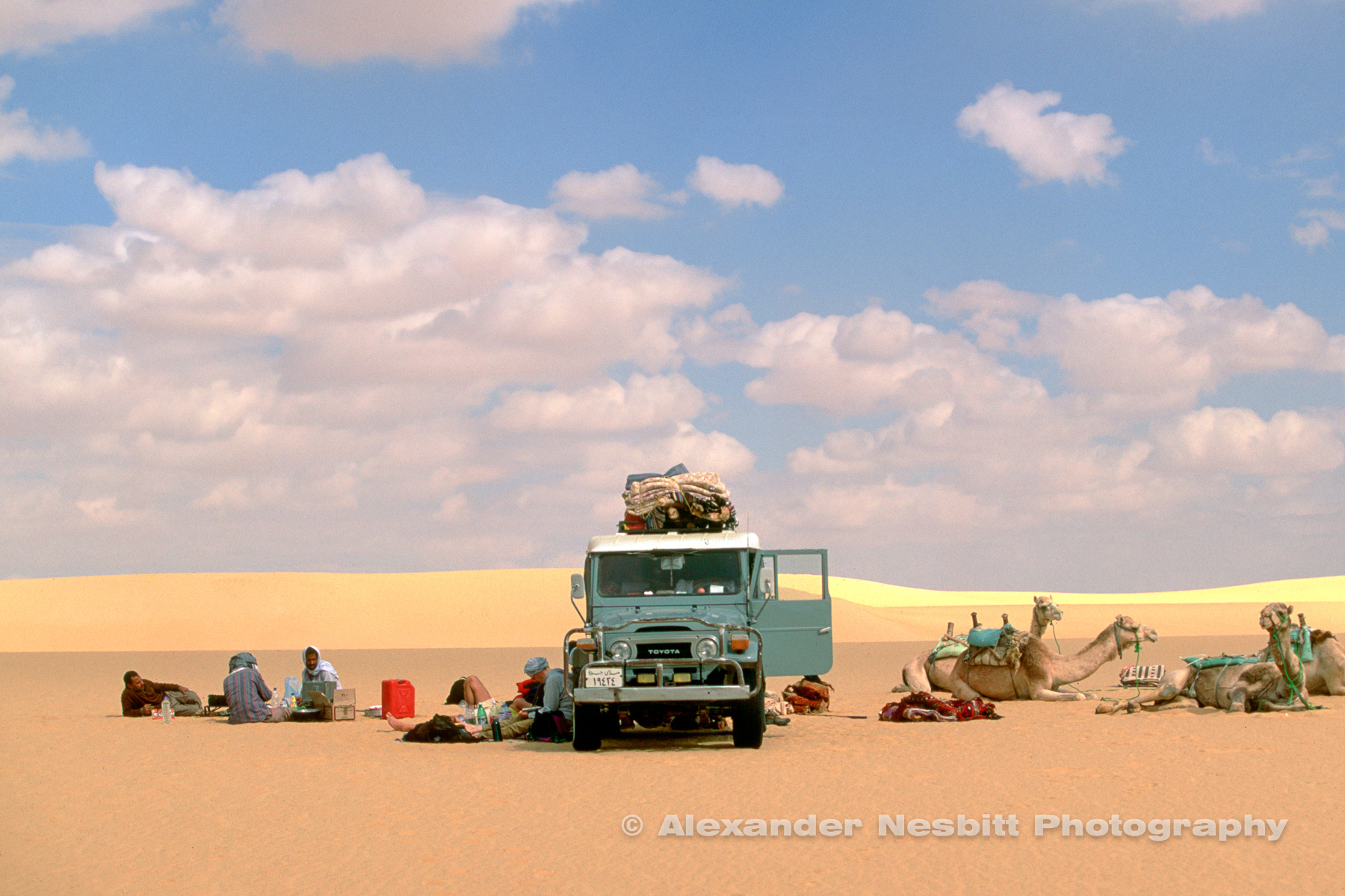 Egypt, 2000 - Egyptian western desert.  Lunch time rendezvous with the supply vehicle, an old FJ40 Landcruiser, midway through a Camel trek  across the sand sea desert between Farafra and Dakhla Oasis.