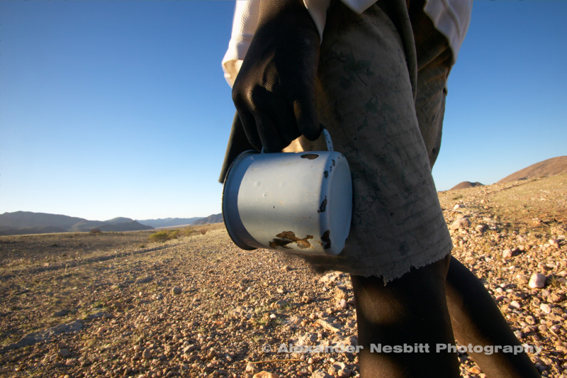 Himba boy with just an old enamel cup passes by heading to waterhole in the hard-scrabble arid region of Kaokoland near Purros, Northern Namibia.