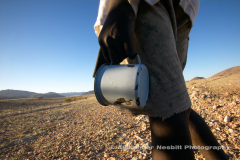 Namibia, 2004 - Himba boy with just an old enamel cup passes by heading to waterhole in the hard-scrabble arid region of Kaokoland near Purros in Northern Namibia.