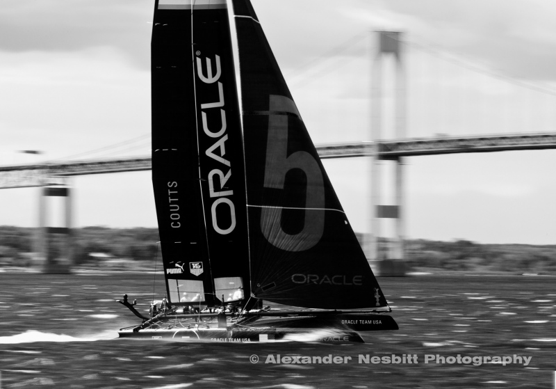 "USA, Newport, RI 2012 - AC45 catamaran Team Oracle with Russell Coutts skippering rips through Naragansett bay past the Newport Bridge during practice rounds of the America's Cup World Championship racing. Intensely careful panning of the 400mm lens with 1/15 second shutter speed brings out the speed blur ""in camera."""