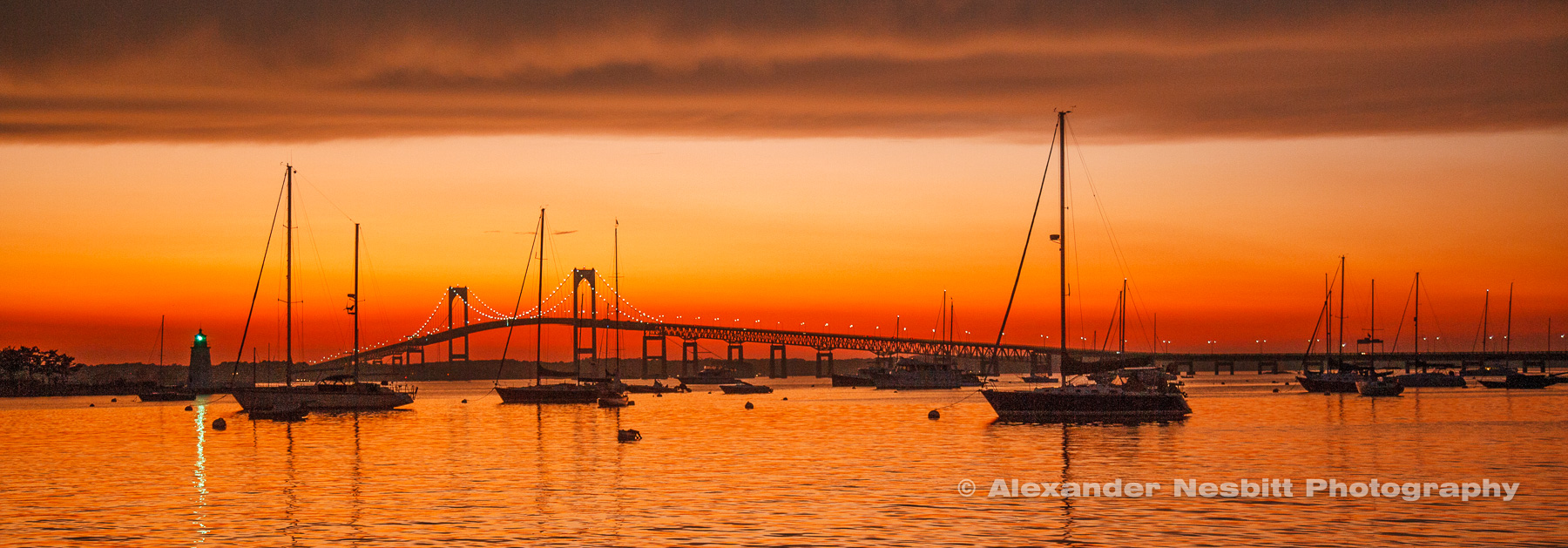 An intense sunset lasting well into dark glows over the Point moorings, the Goat Island Green Light and the Newport Bridge