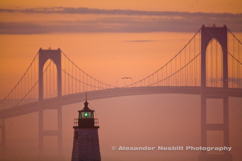 Sunset tints the fog by the greenlight and the Newport Bridge