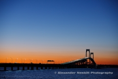 An orange to blue November sunset over the Newport Bridge