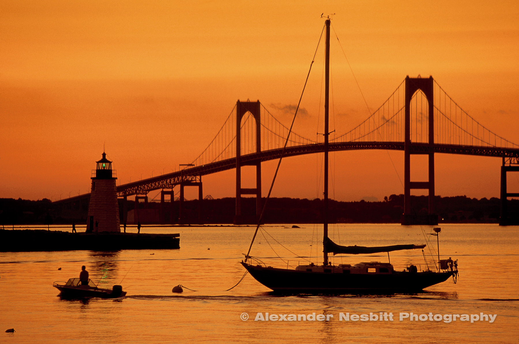 USA, Newport, RI - Orange sunset colors everything - the Newport bridge, the Green light from the lighthouse on Goat Island and a boater passing through.