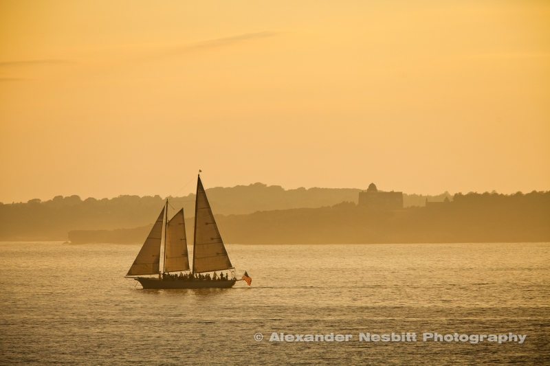 Sailing through a misty, relaxing sunset on Narraganset bay with the Horsehead Mansion on Jamestown in the distance