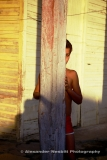 Cuba, 1997- A shy boy ducks behind a porch post of a yellow shack and peers at the photographer with one eye. Jadabonico, Cuba.
