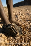 Himba boy with one worn shoe protecting injured toes on the dry desert landscape near Puros, Koakoland, Northern Namibia