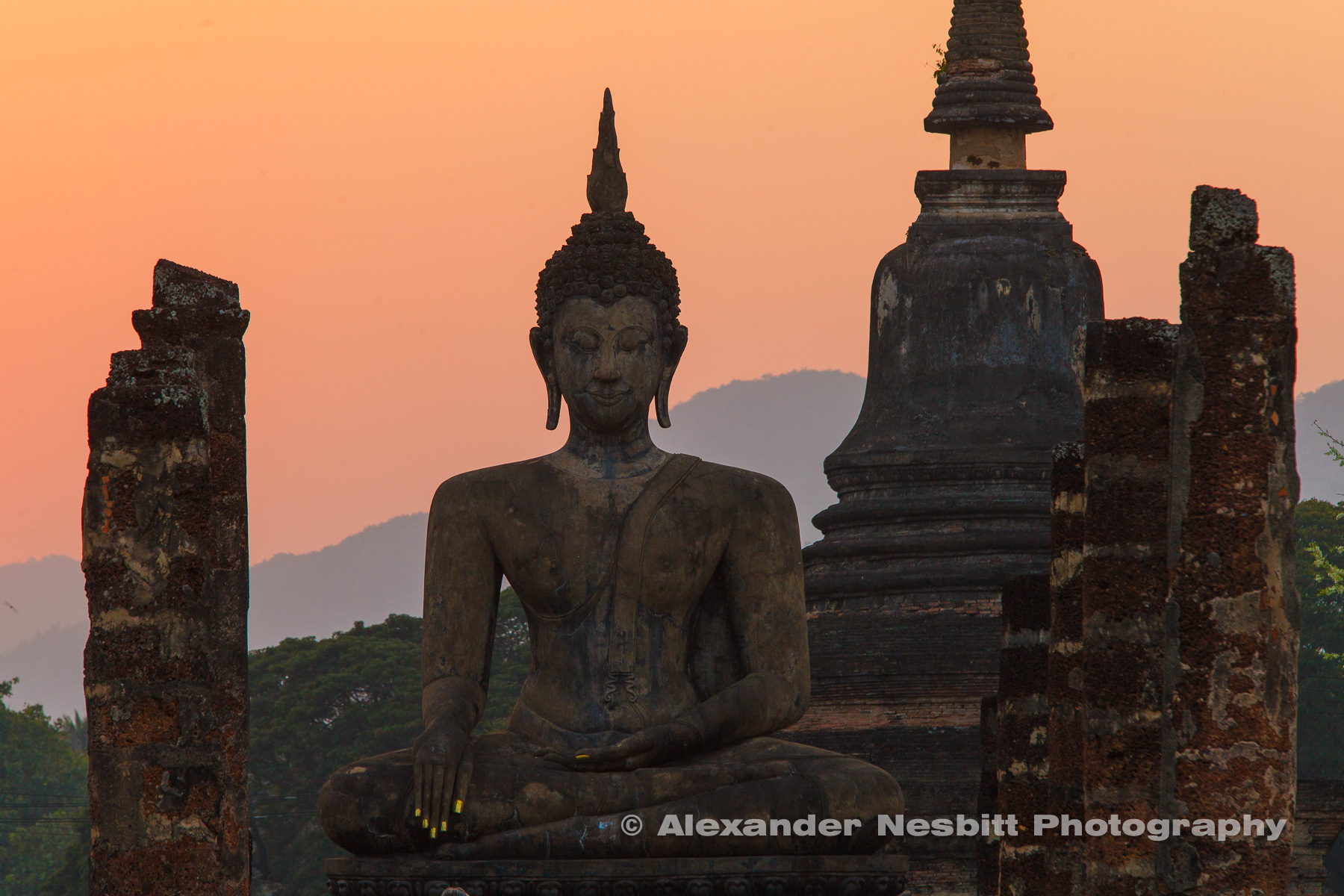 Temple ruins and they reconstructed Buddha silhouetted in the sunset at the ancient complex of Sukothai, Thailand