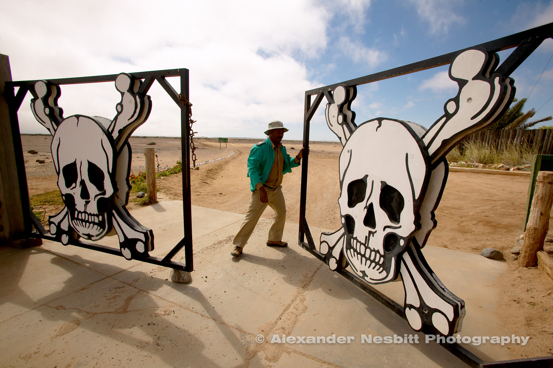 Namibia, 2004 - A giant gate decorated with skulls opens, showing the path to the the famous skelton coast.