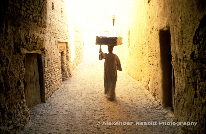 Egypt, 2000 - Man carries crate through the covered passages of 600 year old, mud brick, village of El quasr in Dakhla oasis. As the passage contracts into the distance, the light gets more intense. The man is at the tunnel's end silhouetted by the bright light.