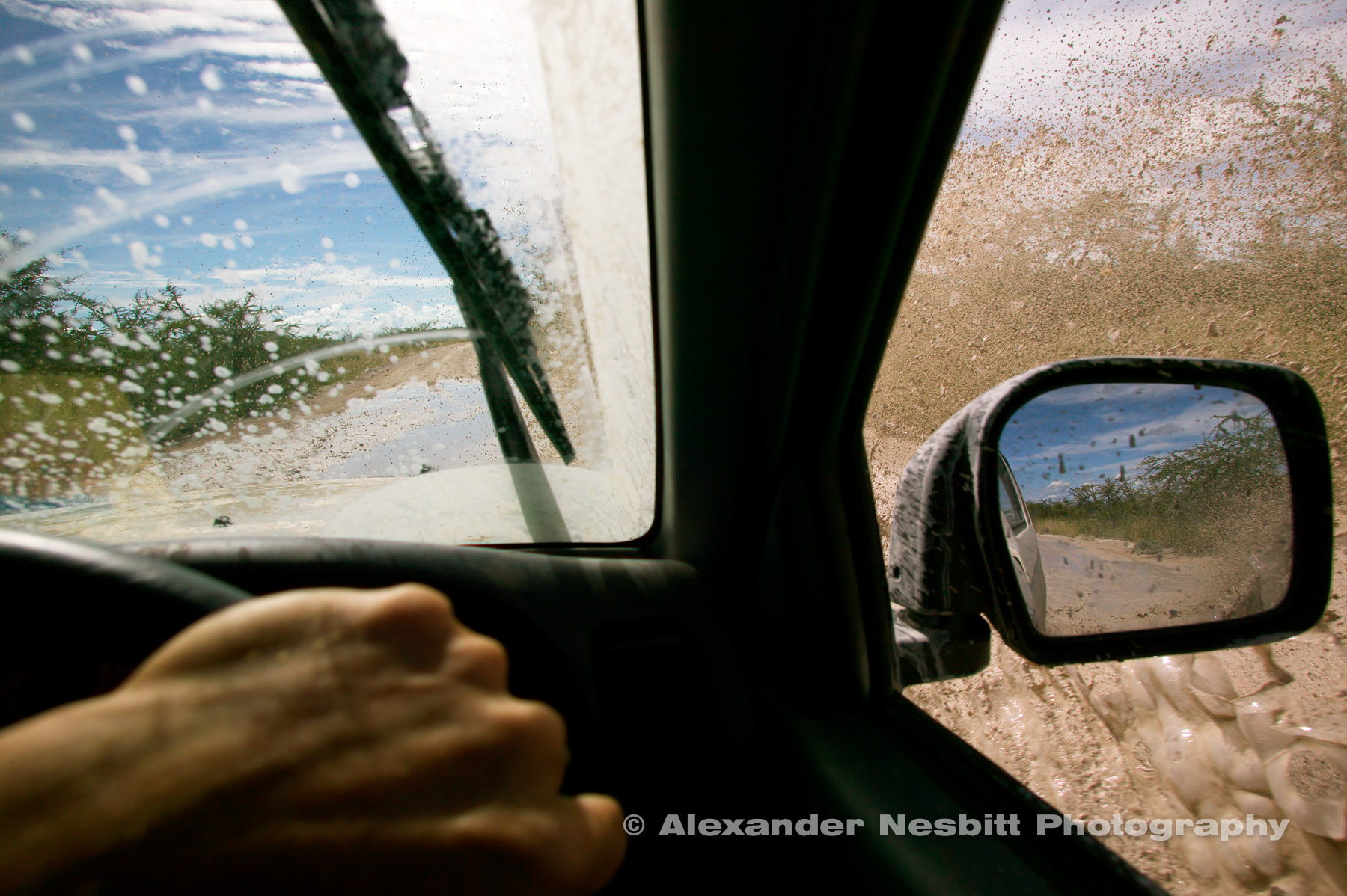 Namibia, Etosha Park 2004 - Drivers hand on wheel of 4x4 while splashing through mud of flooded tracks in Etosha park.